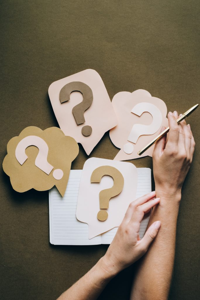 carnet ouvert, main tenant un stylo, et cartons avec points d'interrogation