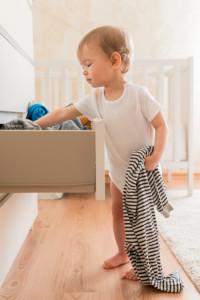 enfant cherche vêtements dans tiroir. vetements à recycler