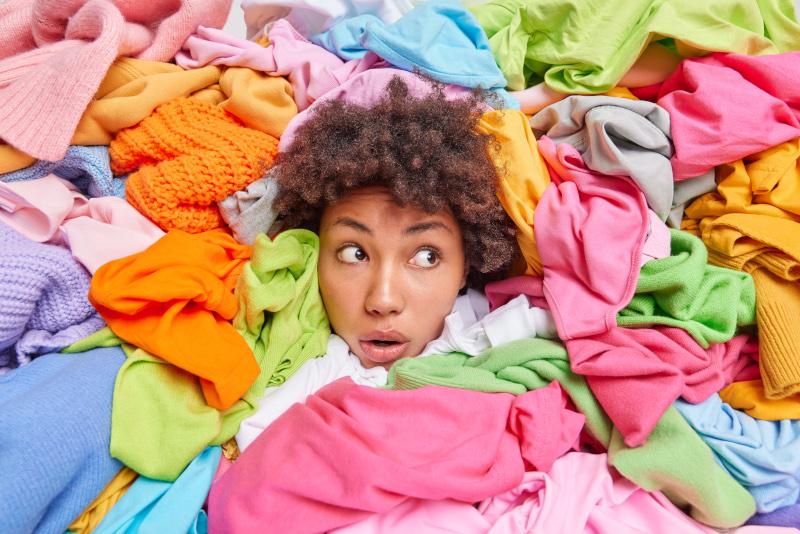 femme sort sa tête d'une montagne de vêtements superflus de sa garde-robe