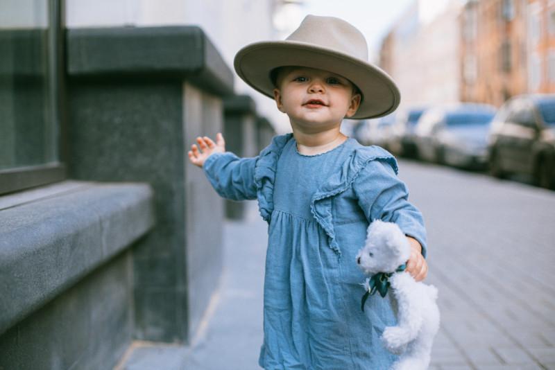 enfant avec doudou porte un chapeau d'adulte